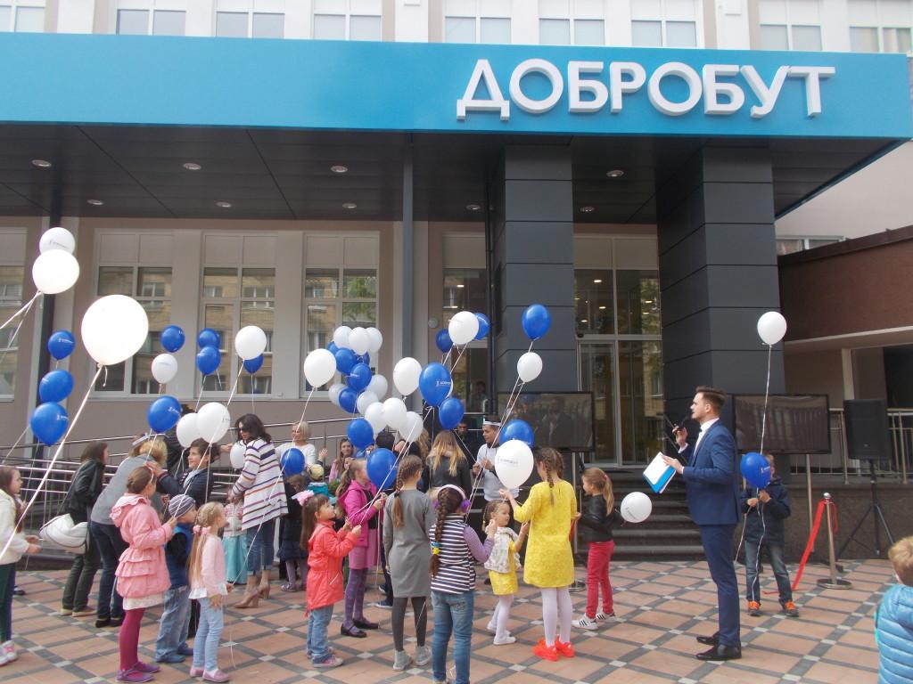 Детки перерезали красную ленту при входе в здание и отпускают в небо воздушные шарики